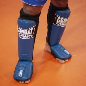 wearing blue combat sports shin guards