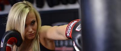 female boxer focuses on the heavy bag
